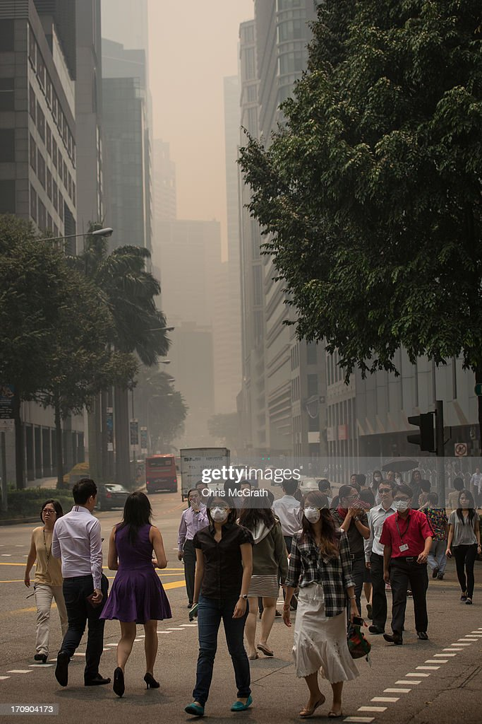 Pedestrians cross a haze filled street in the central business district on June 20, 2013 in Singapore. The Pollutant Standards Index (PSI) rose to the highest level on record reaching 371 at 1pm. The haze is created by deliberate slash-and-burn forest fires started by companies in neighbouring Sumatra.