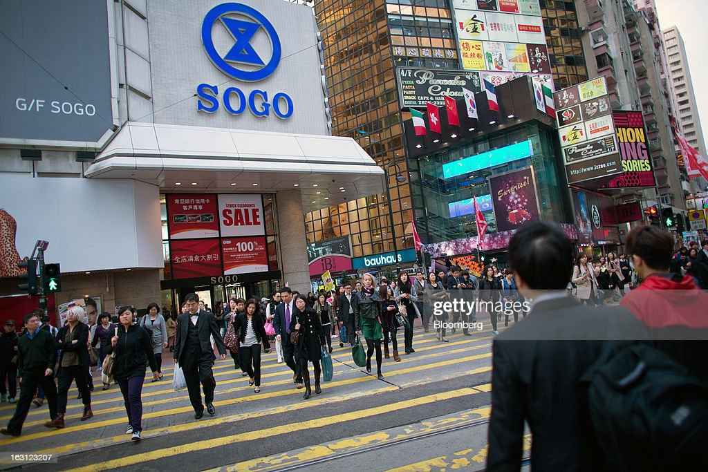 Pedestrians cross a main road in front of the Sogo department store in the Causeway Bay district of Hong Kong, China, on Monday, March 4, 2013. Hong Kong's Causeway Bay overtook New York's Fifth Avenue as the world's most expensive retail location last year, with annual average shop rents reaching $2,630 per square foot at the end of June, a 35 percent increase from a year earlier, according to property broker Cushman & Wakefield Inc. Photographer: Lam Yik Fei/Bloomberg via Getty Images