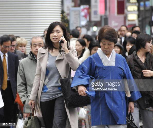 Pedestrians cross a road at Tokyo's Ginza district on November 16 2009 Japan's economy grew at the fastest pace in two and a half years in the third...