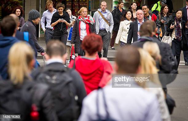 Pedestrians cross a road during the morning rush hour in Sydney Australia on Monday May 7 2012 The Australian government intends to deliver its first...