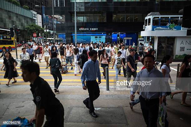 Pedestrians cross a road in front of a Citigroup Inc Citibank branch in the central business district of Hong Kong China on Thursday July 9 2015...