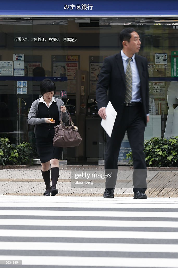 Pedestrians cross a road in front of a Mizuho Bank Ltd. branch in Tokyo, Japan, on Tuesday, Nov. 13, 2012. Mizuho Financial Group Inc. is scheduled to announce first-half earnings results on Nov. 14. Photographer: Kiyoshi Ota/Bloomberg via Getty Images