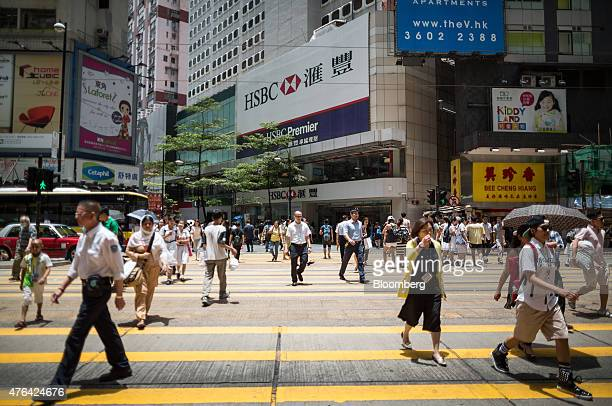 Pedestrians cross a road in front of an HSBC Holdings Plc bank branch in Hong Kong China on Tuesday June 9 2015 HSBC will eliminate as many as 25000...