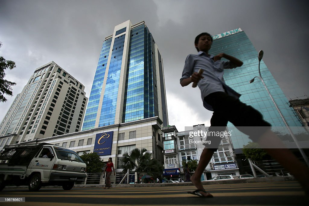 Pedestrians cross a road in front of the AGD Bank tower, right, and the Centrepoint towers in Yangon, Myanmar, on Tuesday, Nov. 20, 2012. Myanmar's growth outlook has improved 'substantially' amid political reforms, which are expected to lead to a large influx of foreign investment, the Organization for Economic Cooperation and Development (OECD) said on Nov. 18. Photographer: Dario Pignatelli/Bloomberg via Getty Images