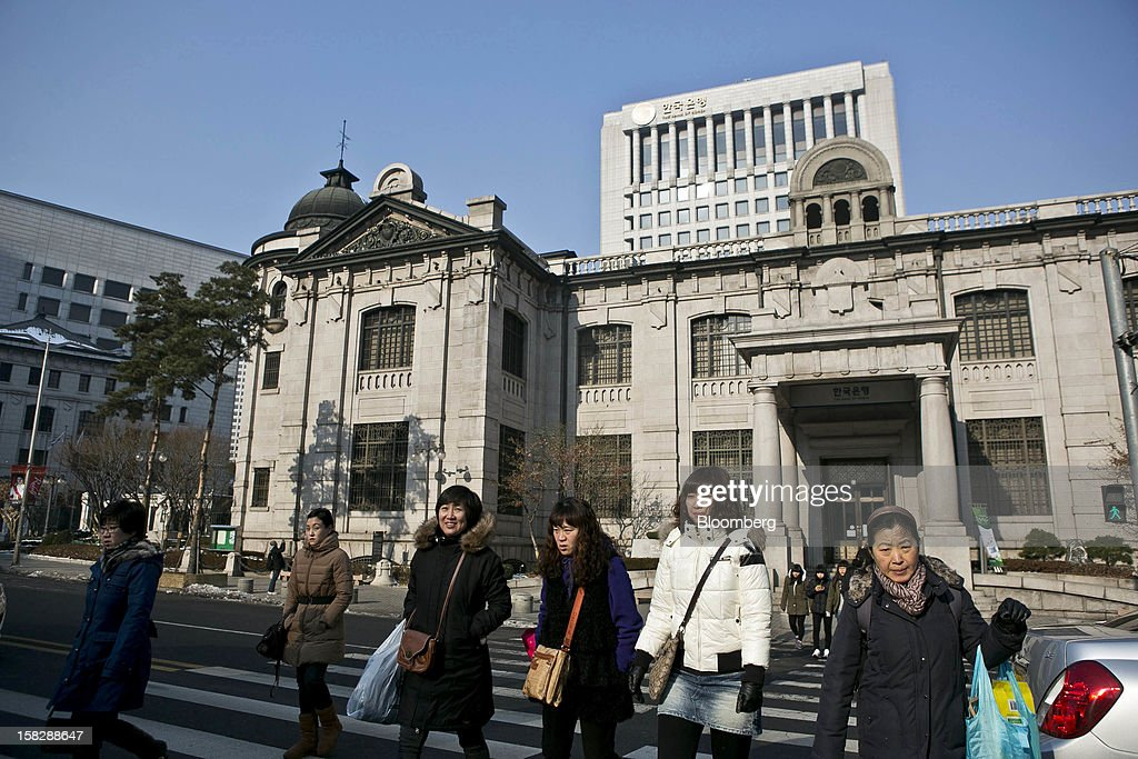 Pedestrians cross a road in front of the Bank of Korea headquarters in Seoul, South Korea, on Thursday, Dec. 13, 2012. The Bank of Korea held borrowing costs unchanged before next week's presidential election and after North Korea launched a rocket in defiance of international sanctions yesterday. Photographer: Jean Chung/Bloomberg via Getty Images