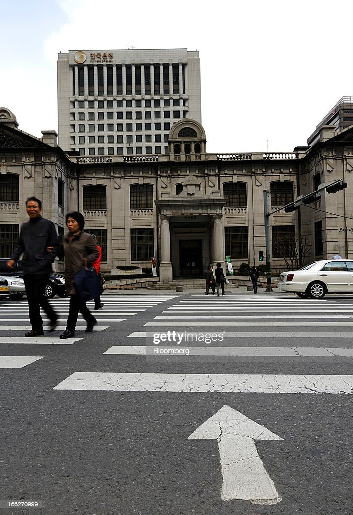 Pedestrians cross a road in front of the Bank of Korea headquarters in Seoul, South Korea, on Thursday, April 11, 2013. The Bank of Korea held borrowing costs unchanged for a sixth month, resisting pressure from the government for a reduction even as a sliding yen hurts the nation's exporters and North Korea threatens war. Photographer: SeongJoon Cho/Bloomberg via Getty Images