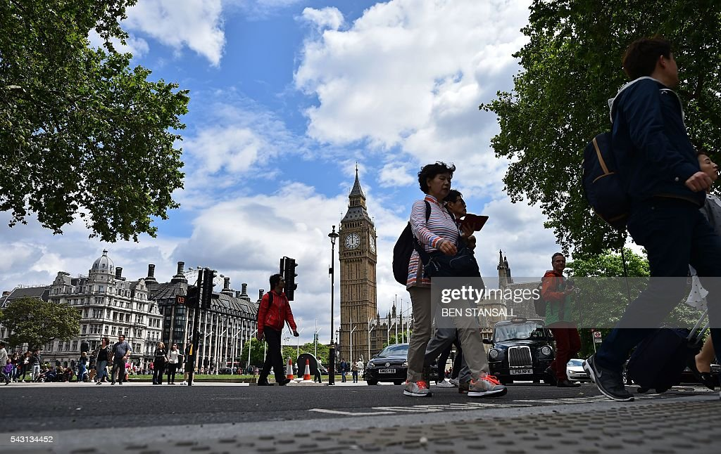 Pedestrians cross a road in front of the Big Ben clock face and the Elizabeth Tower at the Houses of Parliament in central London on June 26, 2016. Britain's opposition Labour party plunged into turmoil Sunday and the prospect of Scottish independence drew closer, ahead of a showdown with EU leaders over the country's seismic vote to leave the bloc. Two days after Prime Minister David Cameron resigned over his failure to keep Britain in the European Union, Labour leader Jeremy Corbyn faced a revolt by his lawmakers who called for him, too, to quit. STANSALL