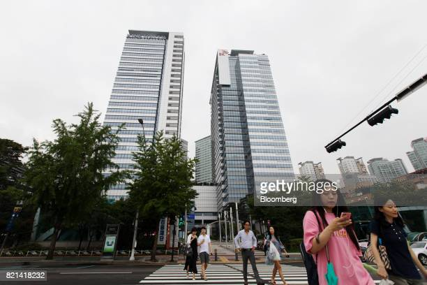 Pedestrians cross a road in front of the SK Hynix Inc office building center right in Seongnam South Korea on Monday July 24 2017 SK Hynix is...