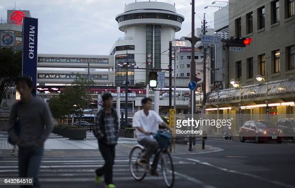 Pedestrians cross a road in front of the Toyota Station in Toyota City Aichi Japan on Thursday Oct 13 2016 Toyota Motor Corp plans to rely on...