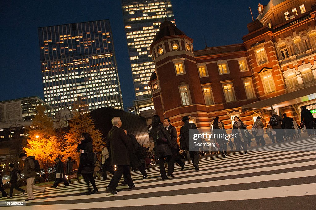 Pedestrians cross a road in front of Tokyo Station in Tokyo, Japan, on Monday, Dec. 10, 2012. Japan's economy shrank in the last two quarters, meeting the textbook definition of a recession, as the dispute with China, the country's biggest export market, caused consumers there to shun Japanese products and contributed to Japan's worst year for exports since the global recession in 2009. Photographer: Noriko Hayashi/Bloomberg via Getty Images
