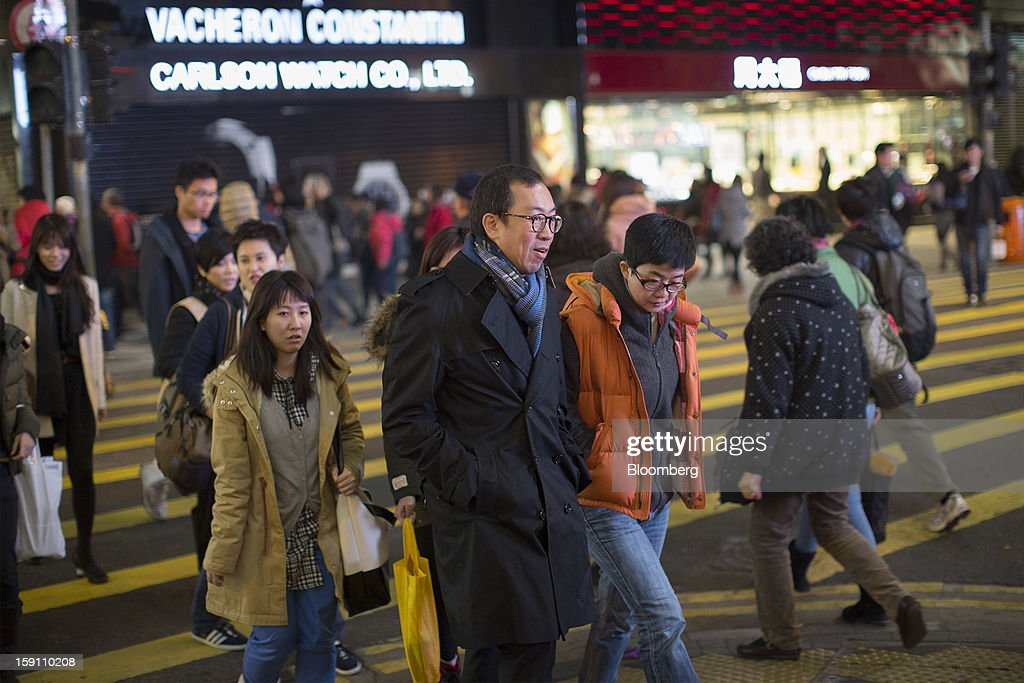 Pedestrians cross a road in the central business district of Hong Kong, China, on Friday, Jan. 4, 2013. Chief Executive Leung Chun-ying, who has been buffeted by student protests and low popularity since taking office on July 1, has pledged to tackle Asia's biggest wealth gap as the division between poor and rich widened to its worst level since at least 1971. Photographer: Jerome Favre/Bloomberg via Getty Images