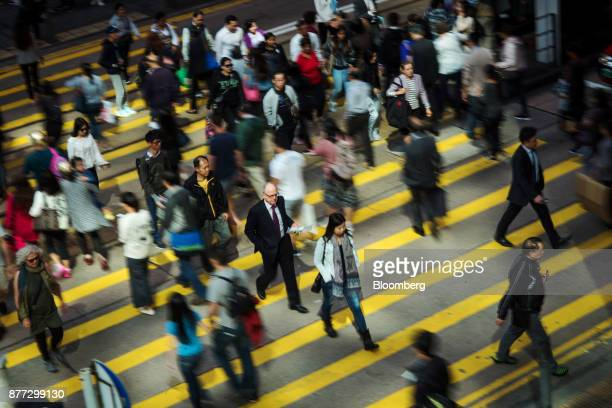 Pedestrians cross a road in the Central district of Hong Kong China on Wednesday Nov 22 2017 Hong Kong's benchmark equity gauge rose above the 30000...