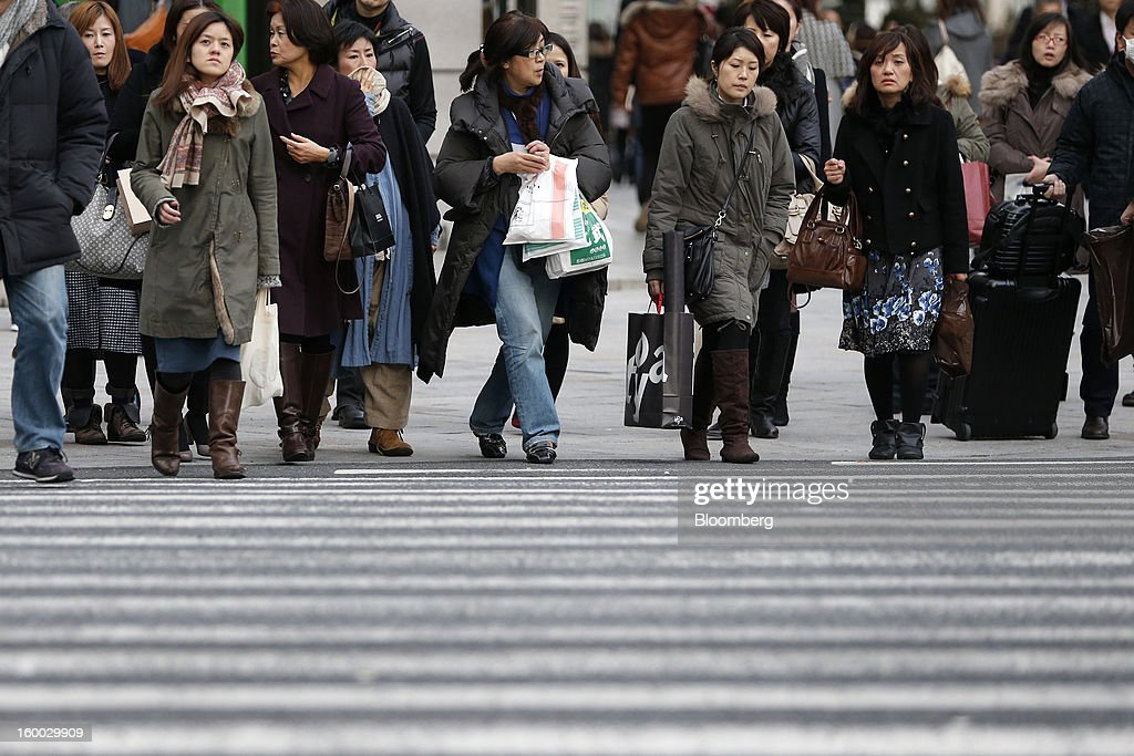 Pedestrians cross a road in Tokyo, Japan, on Friday, Jan. 25, 2013. Japan's consumer prices fell for the seventh time in eight months, underscoring the risk that the central bank may struggle to reach a 2 percent inflation target unless it implements new easing measures earlier than planned. Photographer: Kiyoshi Ota/Bloomberg via Getty Images