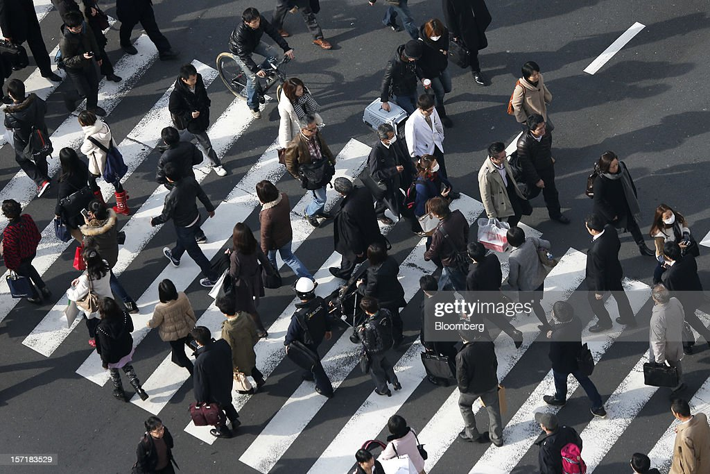 Pedestrians cross a road in Tokyo, Japan, on Thursday, Nov. 29, 2012. Japan's cabinet approved a second round of fiscal stimulus worth 880 billion yen ($10.7 billion) using budget reserves as Prime Minister Yoshihiko Noda attempts to boost the economy before elections on Dec. 16. Photographer: Kiyoshi Ota/Bloomberg via Getty Images