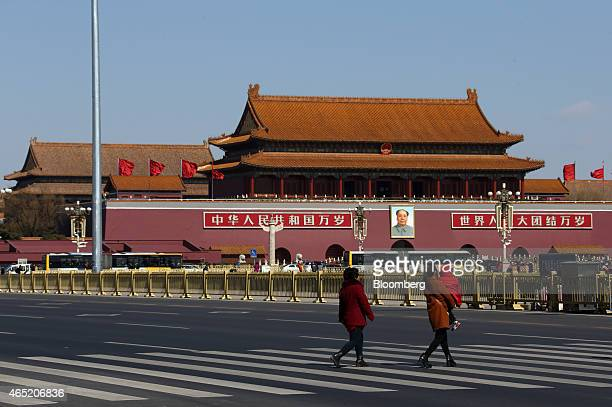 Pedestrians cross a road near Tiananmen Gate in Beijing China on Tuesday March 3 2015 China's annual meeting of the National People's Congress which...