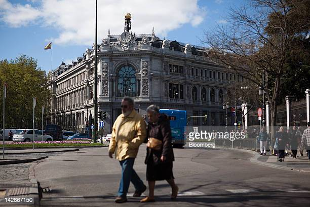Pedestrians cross a road on Cibeles Square near the Bank of Spain or central bank in Madrid Spain on Wednesday April 11 2012 Japan's biggest...