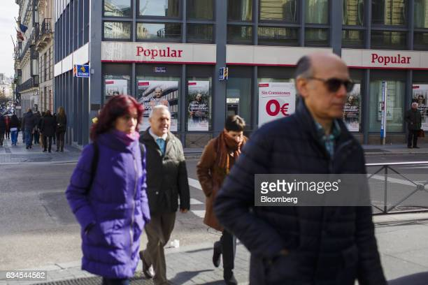 Pedestrians cross a road outside a Banco Popular Espanol SA bank branch in Madrid Spain on Friday Feb 10 2017 Banco Populars new Chairman Emilio...