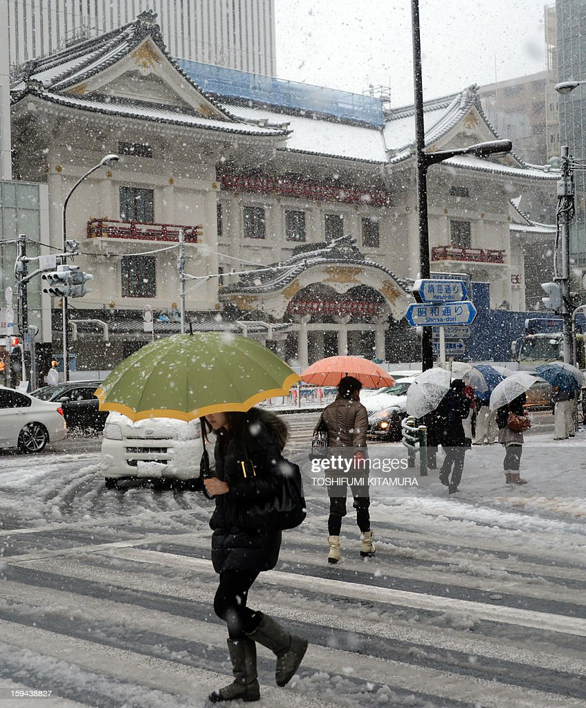 Pedestrians cross a snow-covered street in front of the under-constructing Kabuki theatre (in background) in central Tokyo on January 14, 2013. A storm system grasped central Japan on January 14, causing heavy snow fall around the Japanese capital.