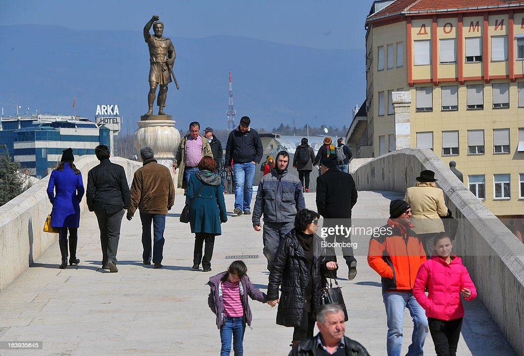 Pedestrians cross a stone bridge connecting Albanian and Macedonian populations in central Skopje, Macedonia, on Sunday, March 17, 2013. Macedonia's economy contracted by a real 0.3% on the year in 2012, compared to a growth of 2.8% a year earlier, an estimate released by the country's statistics office showed. Photographer: Oliver Bunic/Bloomberg via Getty Images