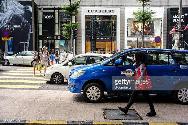 Pedestrians cross a street as a woman walks along a pavement in Kuala Lumpur Malaysia on Friday Aug 5 2016 Malaysia's secondquarter gross domestic...