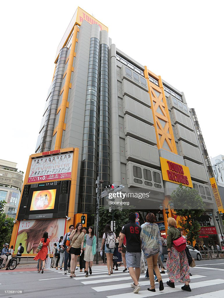 Pedestrians cross a street in front of a Tower Records Japan Inc. store in Tokyo, Japan, on Monday, July 1, 2013. Music sales in the country rose for the first time in five years, led by tunes delivered on CDs and other physical media, bucking the trend in developed markets as cheaper downloads gain ground. Physical media made up 82 percent of Japanese music sales last year, versus 37 percent in the U.S., said the Recording Industry Association of Japan. Photographer: Yuriko Nakao/Bloomberg via Getty Images