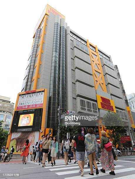 Pedestrians cross a street in front of a Tower Records Japan Inc store in Tokyo Japan on Monday July 1 2013 Music sales in the country rose for the...