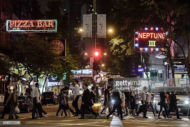 Pedestrians cross a street in front of bars and restaurants in Hong Kong's Wanchai district on November 3 2014 A British banker appeared in a Hong...