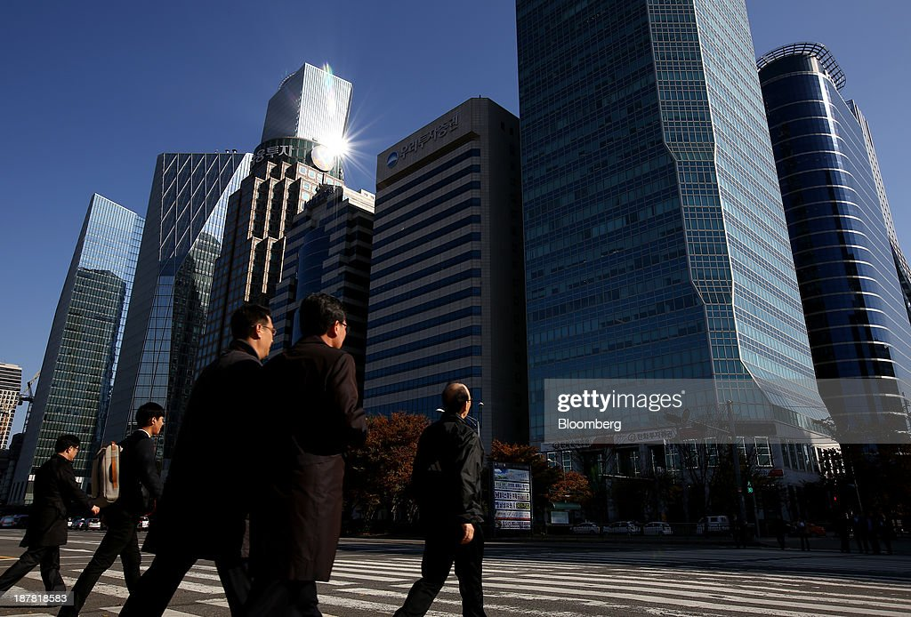 Pedestrians cross a street in front of the headquarters of Woori Investment & Securities Co., center, a unit of Woori Finance Holdings Co., in Seoul, South Korea, on Tuesday, Nov. 12, 2013. Woori Finance Holdings is scheduled to report third-quarter results on Nov. 14. Photographer: SeongJoon Cho/Bloomberg via Getty Images