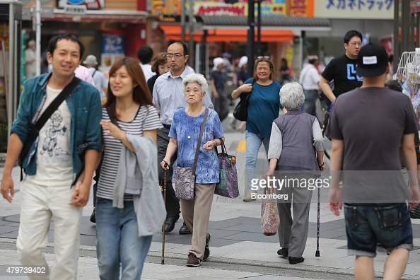 Pedestrians cross a street in Kita ward in Tokyo Japan on Tuesday June 16 2015 Tokyo is one of only four cities among the 71 mostpopulous urban...
