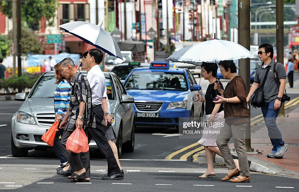 Pedestrians cross a street in Singapore on January 2, 2013. Singapore's economy grew in the fourth quarter, avoiding a technical recession despite disappointing growth figures for 2012, government data showed on January 2. AFP PHOTO / ROSLAN RAHMAN