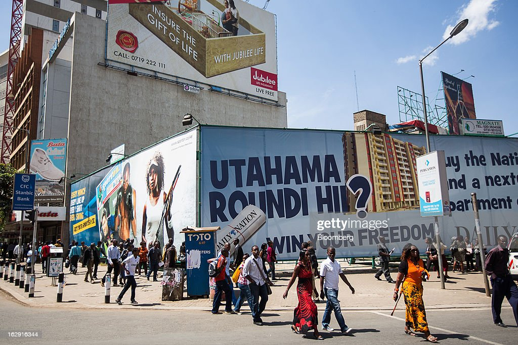 Pedestrians cross a street near advertising posters in Nairobi, Kenya, on Friday, March 1, 2013. Next week's presidential vote will be the first since disputed elections in 2007 triggered ethnic fighting in which more than 1,100 people died and another 350,000 fled their homes. Photographer: Trevor Snapp/Bloomberg via Getty Images