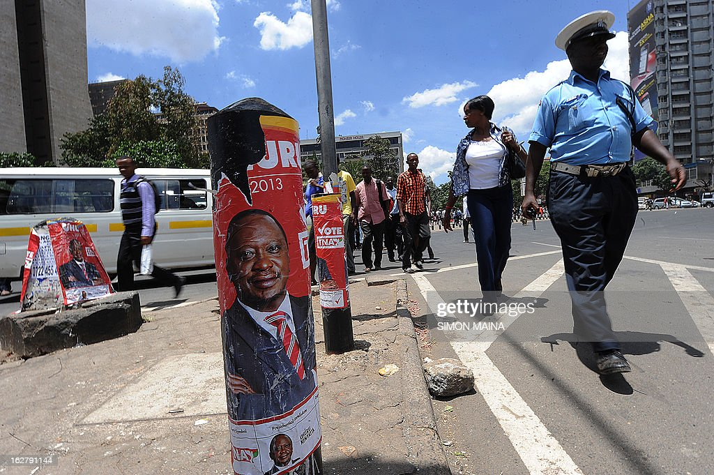 Pedestrians cross a street next to a campaign billboards advertising Presidential candidate Uhuru Kenyatta, on the outskirts of Nairobi, Kenya on February 27, 2013. Kenya is gearing up for presidential, gubernatorial, senatorial elections on March 4, the first since bloody post-poll violence five years ago in which more than 1,100 people died after contested results.