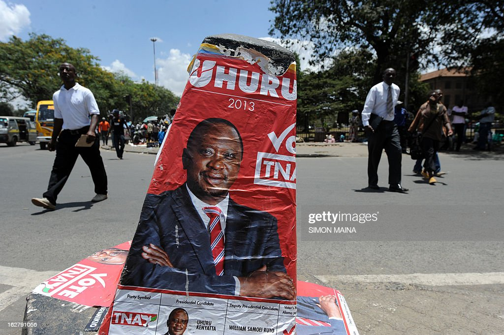 Pedestrians cross a street next to a campaign poster advertising Presidential candidate Uhuru Kenyatta and his running-mate William Ruto, on the outskirts of Nairobi, Kenya on February 27, 2013. Kenya is gearing up for presidential, gubernatorial, senatorial elections on March 4, the first since bloody post-poll violence five years ago in which more than 1,100 people died after contested results. AFP PHOTO/SIMON MAINA