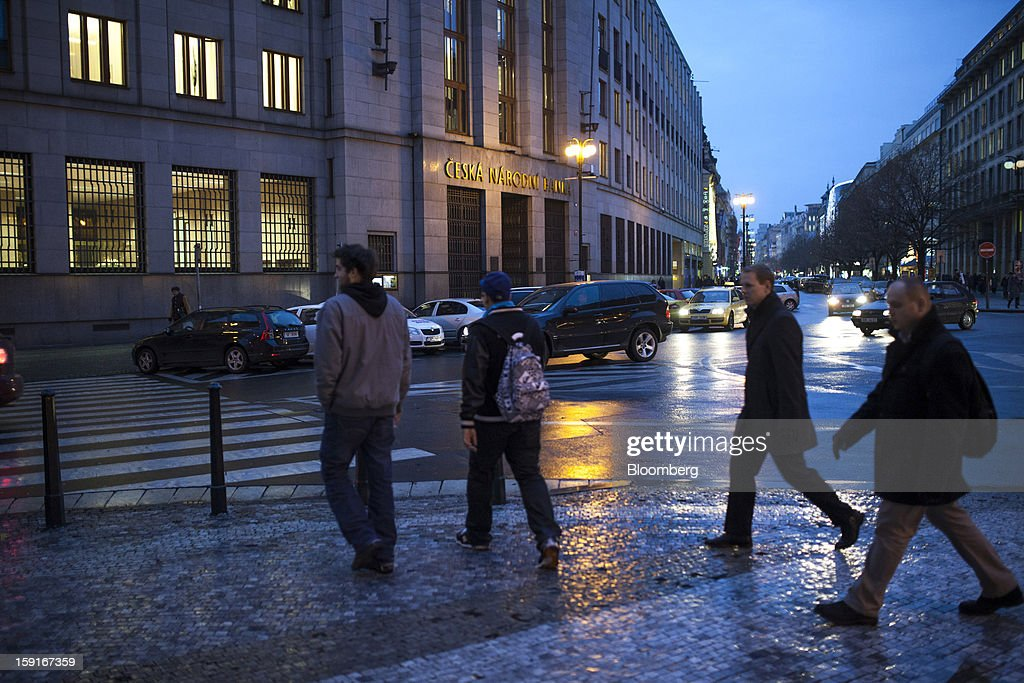Pedestrians cross a street outside the Czech central bank, center, in the financial district of Prague, Czech Republic, on Tuesday, Jan. 8, 2013. The Czech economy is showing weak domestic demand as households and businesses cut spending due to government austerity programs and the euro area's debt crisis. Photographer: Bartek Sadowski/Bloomberg via Getty Images