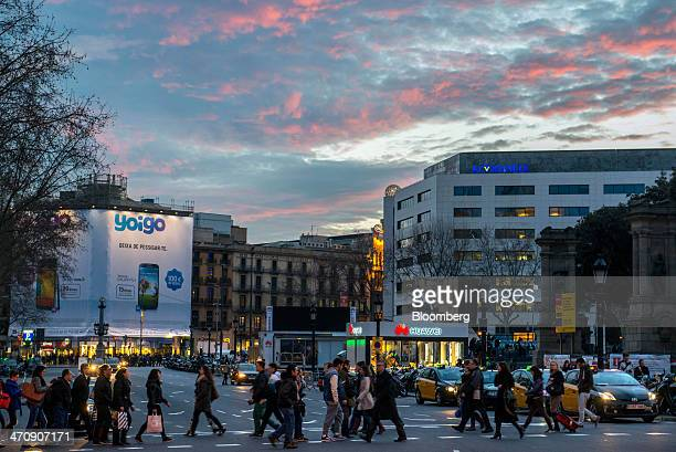 Pedestrians cross a street past an illuminated advertisement for Yoigo and a Huawei Technologies Co store in Barcelona Spain on Thursday Feb 20 2014...