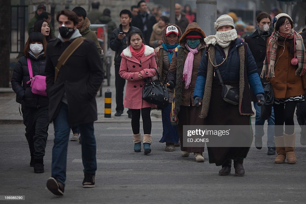 Pedestrians cross a street, some wearing face masks, during polluted weather in Beijing on January 13, 2013. Dense smog shrouded Beijing, with pollution at hazardous levels for a second day and residents advised to stay indoors, state media said. AFP PHOTO / Ed Jones