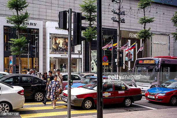 Pedestrians cross a street through traffic in Kuala Lumpur Malaysia on Friday Aug 5 2016 Malaysia's secondquarter gross domestic product figures are...