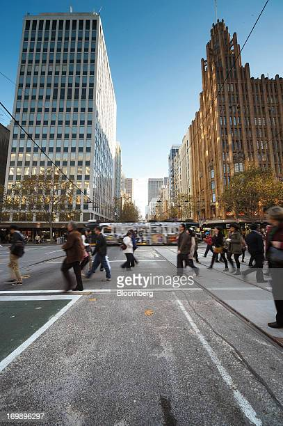 Pedestrians cross an intersection at Collins Street and Swanston Street in central Melbourne Australia on Sunday June 2 2013 The Australian Bureau of...