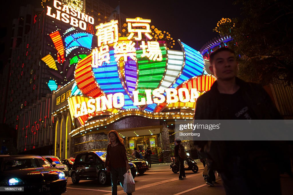 Pedestrians cross an intersection in front of the Casino Lisboa, operated by SJM Holdings Ltd., in Macau, China, on Wednesday, Feb. 6, 2013. Casino industry revenue in the gambling hub climbed 14 percent to a record 304 billion patacas ($38 billion) last year. Photographer: Lam Yik Fei/Bloomberg via Getty Images
