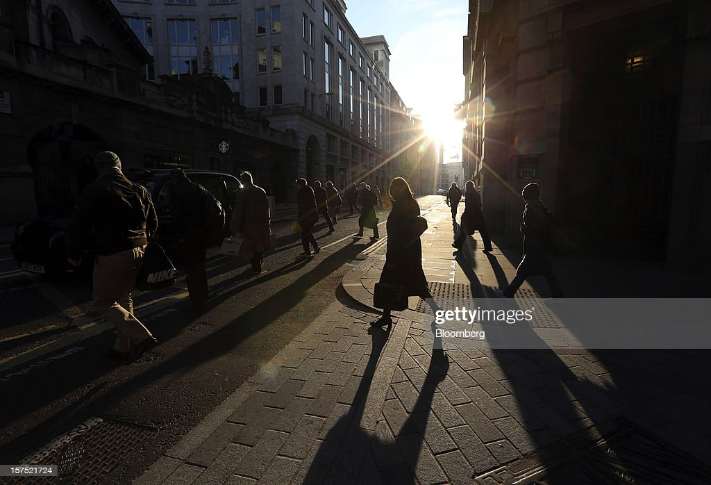Pedestrians cross an intersection in the financial district in London, U.K., on Friday, Nov. 30, 2012. U.K. banks have become more unwilling to finance development projects without a tenant committed to lease space or a buyer for the completed property. Photographer: Chris Ratcliffe/Bloomberg via Getty Images