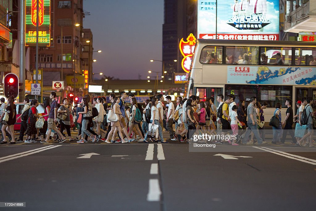 Pedestrians cross an intersection in the Mong Kok district of Hong Kong, China, on Sunday, June 30, 2013. Hong Kongs best-selling newspapers called on readers to join a march to mark the anniversary of the citys handover to China, saying the government has failed to address issues of poverty and universal suffrage. Photographer: Jerome Favre/Bloomberg via Getty Images