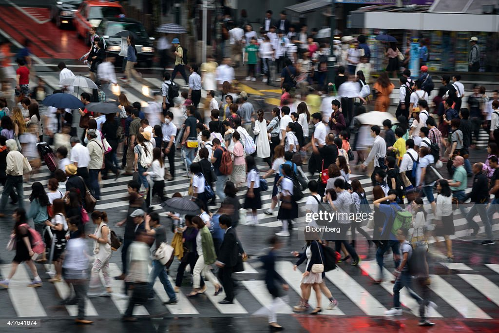 Pedestrians cross an intersection in the Shibuya district of Tokyo Japan on Wednesday June 17 2015 Bank of Japan Governor Haruhiko Kuroda said last...