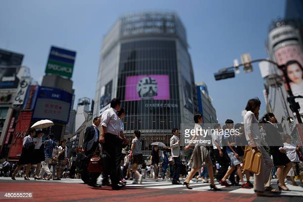 Pedestrians cross an intersection in this photograph taken with a tiltshift lens in the Shibuya district of Tokyo Japan on Friday July 10 2015 Bank...