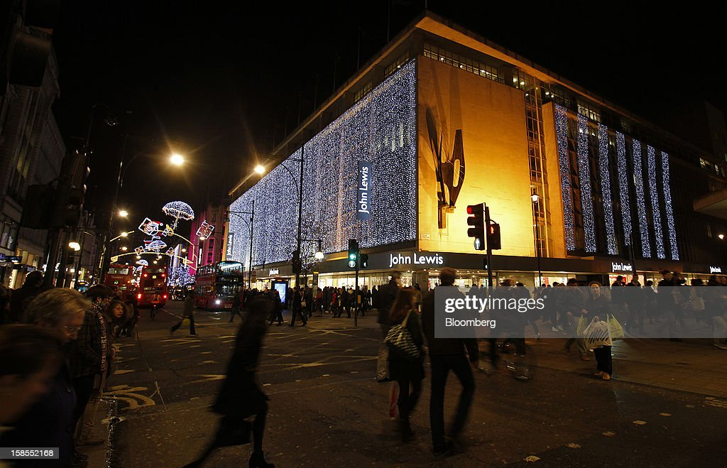 Pedestrians cross an intersection near the seasonally decorated John Lewis Plc store on Oxford Street in London, U.K., on Monday, Dec. 17, 2012. Retailers are relying on Christmas sales to help rescue a year when high unemployment and the debt crisis have blighted spending. Photographer: Simon Dawson/Bloomberg via Getty Images