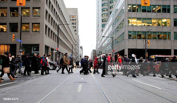 Pedestrians cross Bay Street in the financial district of Toronto Ontario Canada on Tuesday Feb 5 2013 Canada's dollar declined from almost a twoweek...