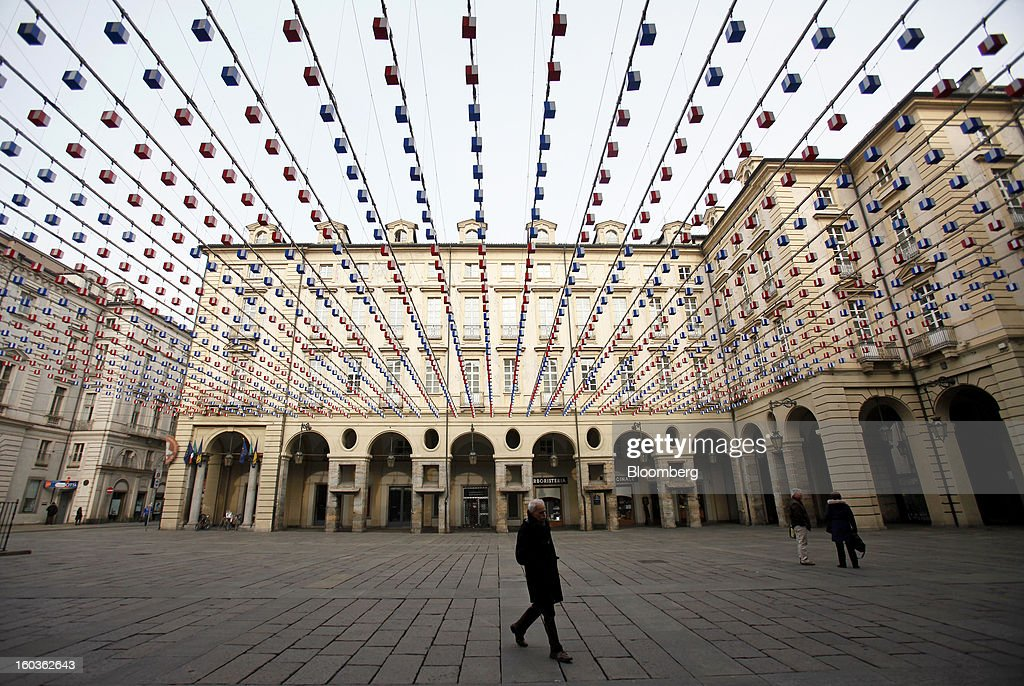 Pedestrians cross Palazzo di Citta square in Turin, Italy, on Tuesday, Jan. 29, 2013. Italy sold 8.5 billion euros ($11.4 billion) of six-month Treasury bills as rates dropped to the lowest in almost three years as the European Central Bank's pledge to buy bonds continues to provide an effective backstop even amid rising political concerns. Photographer: Alessia Pierdomenico/Bloomberg via Getty Images