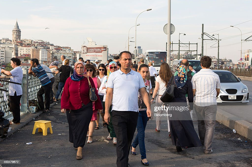 Pedestrians cross the Galata bridge in the Eminonu district of Istanbul, Turkey, on Sunday, Aug. 10, 2014. Investors said they will need to assess the next government's commitment to financial stability should Turkish Prime Minister Recep Tayyip Erdogan assume the presidency this month. Photographer: Kerem Uzel/Bloomberg via Getty Images