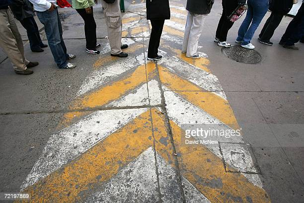 Pedestrians cross the international border from Mexico to the United States on the morning that the US population hit the historic milestone of 300...