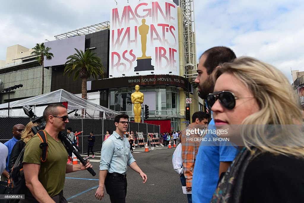 Pedestrians cross the intersection of Hollywood Boulevard and Highland Avenue in Hollywood California on February 21 2015 where a large statue of the...