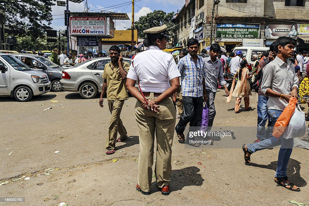 Pedestrians cross the road as a female traffic police officer looks on in Bangalore, India, on Saturday, Oct. 12, 2013. Reserve Bank of India Governor Raghuram Rajan has turned the rupee from a pariah to the worlds favorite currency after just a month in office as he intensifies efforts to quell inflation and lure capital. Photographer: Dhiraj Singh/Bloomberg via Getty Images
